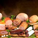 Collection of cold cuts sliced on wooden boards surrounded by herbs, vegetables and spices.